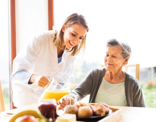 caregiver serving a juice to the senior woman
