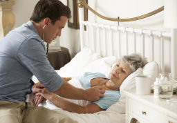 Doctor Examining Senior Female Patient In Bed At Home