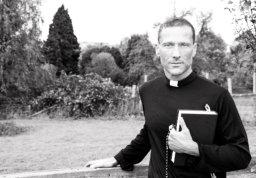 priest standing with one hard on gate while holding bible with orchard